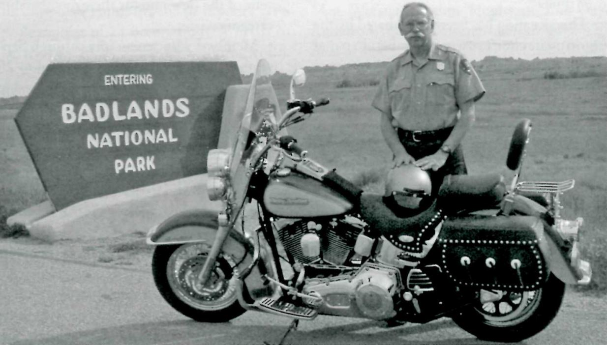 Bill Supernaugh next to his motorcycle at the entrace to Badlands National Park